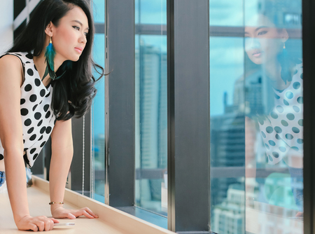 Asian attractive woman thinking and looking out window Stock fotó