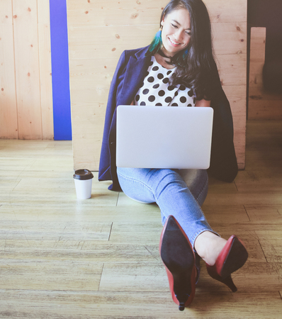 Beautiful fashionable asian woman working with laptop on the wooden floor