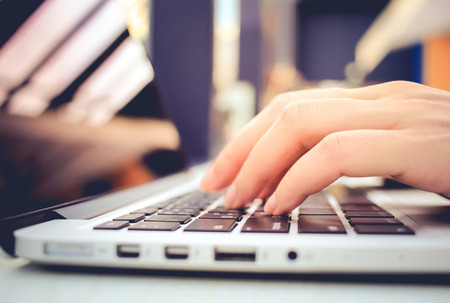 Female hands typing on keyboard of laptop