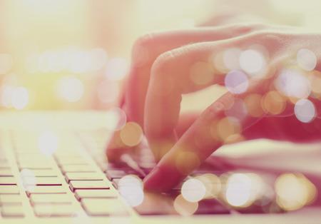 mecanografía: Doble exposición de las manos femeninas escribiendo en la computadora portátil con la luz del bokeh Foto de archivo