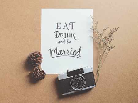 camera: Eat drink and be married quote on paper with vintage film camera