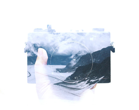 multiple exposure: Double exposure of hand holding film camera and landscape background Stock Photo