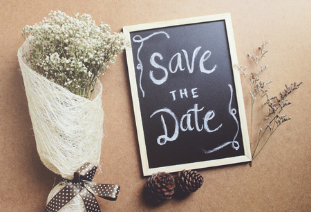 dattes: Save the date written on blackboard with bouquet of flower, retro filter effect