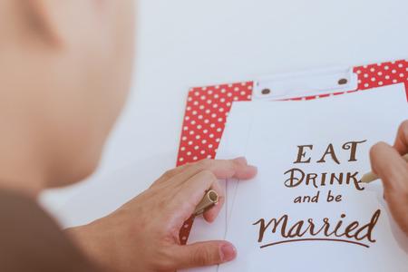 男人寫作吃喝喝,結婚報價在紙卡上,用於婚禮概念