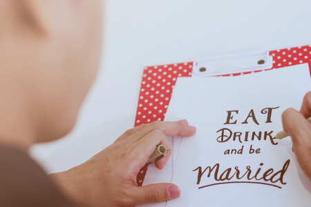 Man writing eat drink and be married quote on paper card for wedding concept