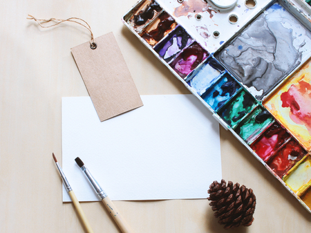 artistic: Artist workspace mock up with brush and paint on blank card
