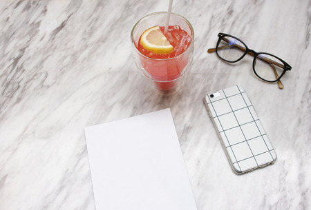 Smartphone and iced soft drink with blank paper on marble table Stock Photo