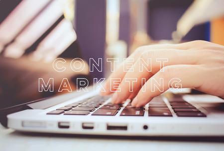 Mani femminili digitando sulla tastiera del computer portatile con contenuti marketing parola Archivio Fotografico