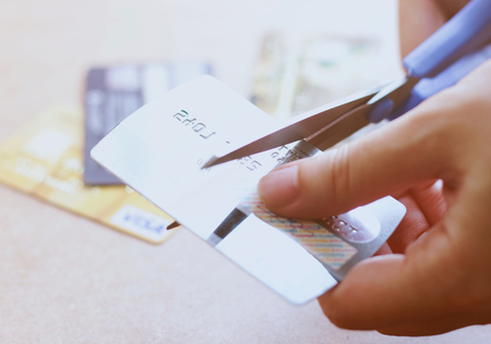 banking problems: Hand cutting credit card with scissors on table? Stock Photo