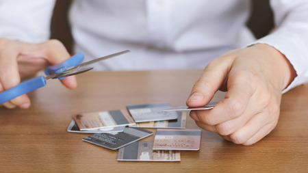 scissors: Hand cutting credit card with scissors on table? Stock Photo