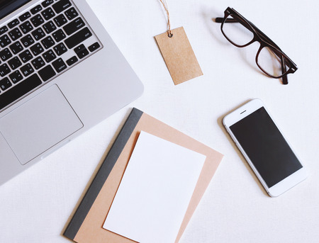 Flat lay photo of office desk with laptop, smartphone, eyeglasses and notebook with copy space background Stock Photo