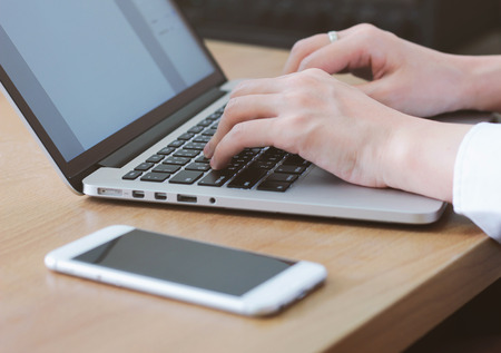 macros: woman typing on laptop with smartphone on the table in office or home Stock Photo