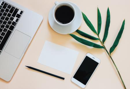 Creative plat foto van werkruimte bureau met laptop, smartphone, koffie en blanco papier met een kopie ruimte achtergrond, minimalistische stijl Stockfoto