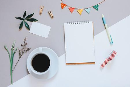Creatieve platte lay-out van een leuke werkruimte bureau met notitieboekje, koffie, naamkaart en versierd schattig ambacht met kopie ruimte achtergrond, minimale stijl