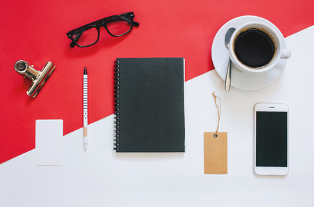 Creative flat lay photo of workspace desk with smartphone, eyeglasses, coffee, tag and notebook with copy space background, minimal styled 스톡 콘텐츠