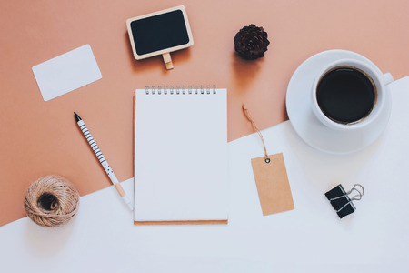 Creative flat lay photo of workspace desk with smartphone, coffee, tag and notebook with copy space background, minimal styled Stock Photo
