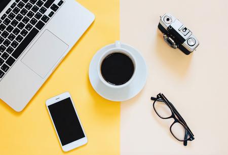 Creativo piatta foto laici della scrivania di lavoro con computer portatile, smartphone, caffè, occhiali da vista e cinepresa su sfondo giallo moderno