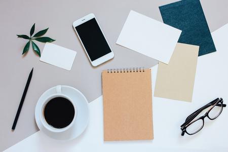 papeleria: foto en plano creativo de escritorio del área de trabajo con el teléfono inteligente, café, etiqueta, carta y bloc de notas con copia espacio de fondo, estilo minimalista