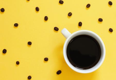 Bovenaanzicht van zwarte koffie en koffiebonen op gele achtergrond
