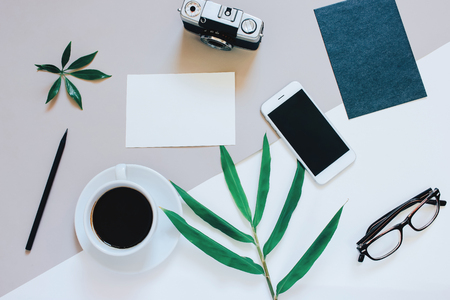 Creative flat lay photo of workspace desk with smartphone, coffee, film camera, blank paper and envelope with copy space background, minimal style