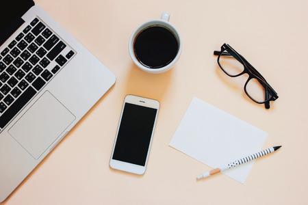 創造的なフラットは、ノート パソコン、スマート フォン、コーヒー、コピー領域の背景、最小限のスタイルで白紙とワークスペースの机の写真を置