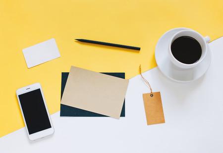 Creative flat lay photo of workspace desk with smartphone, coffee, tag and letter with copy space background, minimal styled Stock Photo