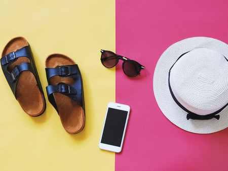 Flat lay style of summer accessories and travel items on colorful background