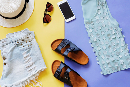 Flat lay style of summer clothes and accessories on colorful background