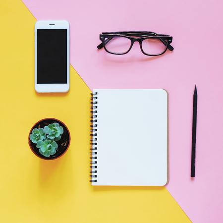 Creatieve platte lay-out van werkruimte bureau met smartphone, bril, cactus en notebook met kopie ruimte achtergrond, minimale stijl