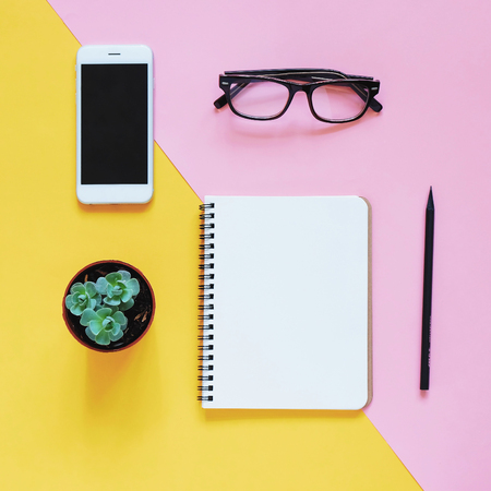 Creativo piatta foto laici della scrivania di lavoro con lo smartphone, occhiali da vista, cactus e notebook con sfondo copia spazio, stile minimal Archivio Fotografico - 57081683