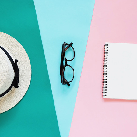 Creative flat lay photo of fashion style with eyeglasses, panama hat and notebook with copy space background, minimal style