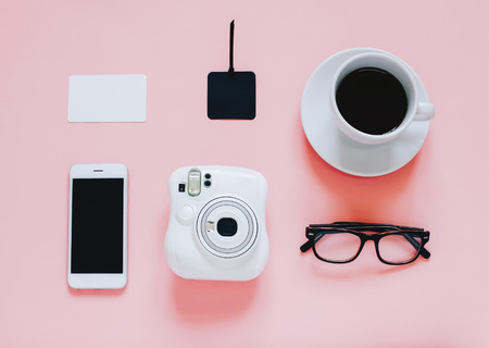 Creative flat lay photo of workspace desk with instant camera, coffee, tag, smartphone and eyeglasses on pink background Standard-Bild