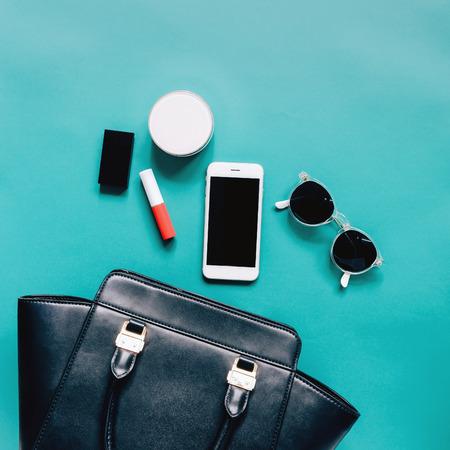aplanada de la mujer del bolso de cuero negro se abren con los cosméticos, los accesorios y el teléfono inteligente en el fondo verde
