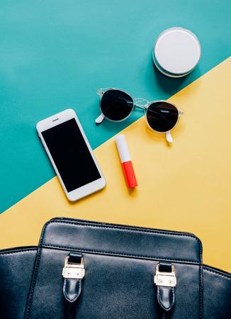 en plano de la mujer bolsa de cuero negro se abren con los cosméticos, los accesorios y el teléfono inteligente en el fondo colorido Foto de archivo