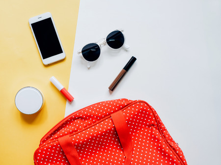 Flat lay of red polka dot woman bag open out with cosmetics, accessories and smartphone on colorful background Stockfoto