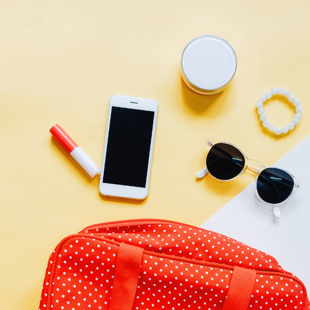 Flat lay of red polka dot woman bag open out with cosmetics, accessories and smartphone on colorful background Banque d'images