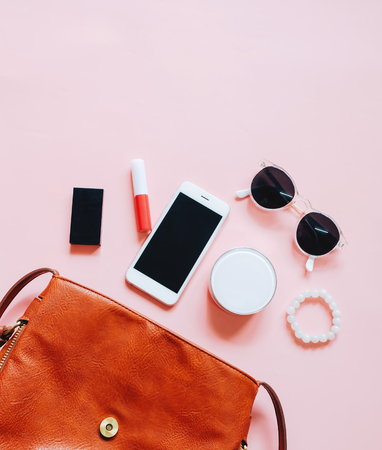 Düz koyu kahverengi deri kadın çantası açık kozmetik, aksesuarlar ve akıllı telefon pembe arka planda