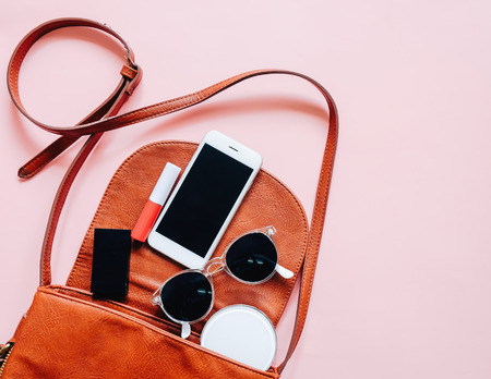 Flat lay of brown leather woman bag open out with cosmetics, accessories and smartphone on pink background