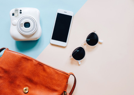 Flat lay of brown leather woman bag open out with accessories, instant camera and smartphone on colorful background