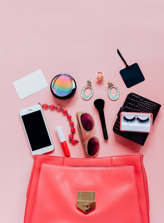 Flat lay of pink leather woman bag open out with cosmetics, accessories, tag card and smartphone on pink background with copy space