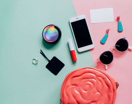 Flat lay of pink cute woman bag open out with cosmetics, accessories, tag card and smartphone on colorful background with copy space Stockfoto