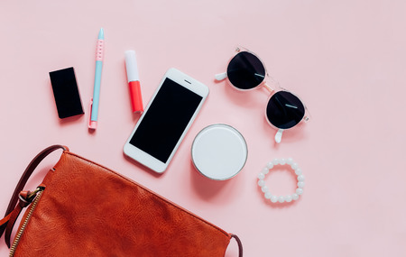 Flat lay of brown leather woman bag open out with cosmetics, accessories and smartphone on pink background with copy space Banco de Imagens