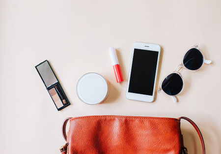 Flat lay of brown leather woman bag open out with cosmetics, accessories and smartphone on yellow background with copy space 스톡 콘텐츠