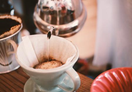 Hand drip koffie, barista gieten water op gemalen koffie met een filter druppelen stijl Stockfoto