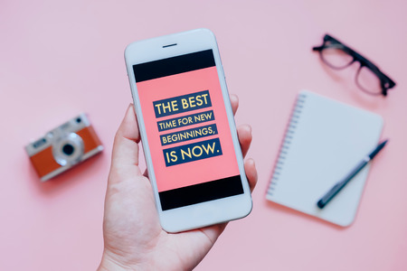 Hand holding smartphone and inspirational quote on screen with camera, notebook and eyeglasses on pink background