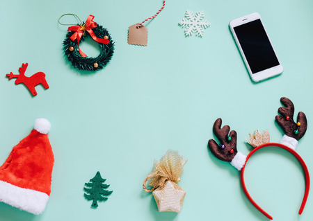 휴일 개념 : 평면 크리스마스 장신구 및 복사 공간와 녹색 배경에 스마트 폰 액세서리의 누워