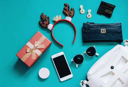 Fashion concept : Flat lay of white woman bag open out with accessories, cosmetics, gift box, smartphone, wallet and hair band on green background