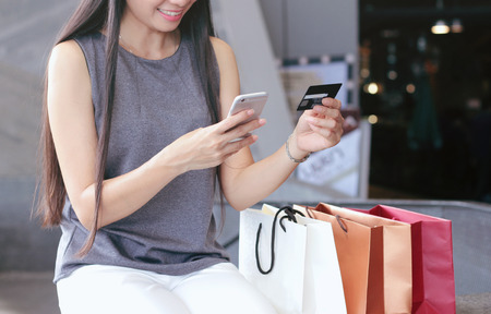 shopping card: Woman hands holding credit card and shopping online through smartphone while sitting beside shopping bag in the department store Stock Photo