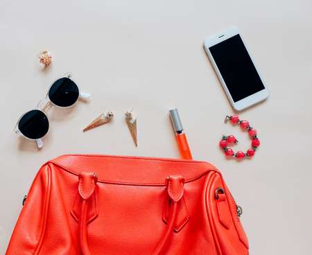 cosmetics background: Flat lay of red leather woman bag open out with cosmetics, accessories and smartphone on yellow background Stock Photo