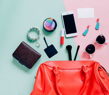 Flat lay of pink cute woman bag open out with cosmetics, accessories, tag card and smartphone on colorful background with copy space Banque d'images